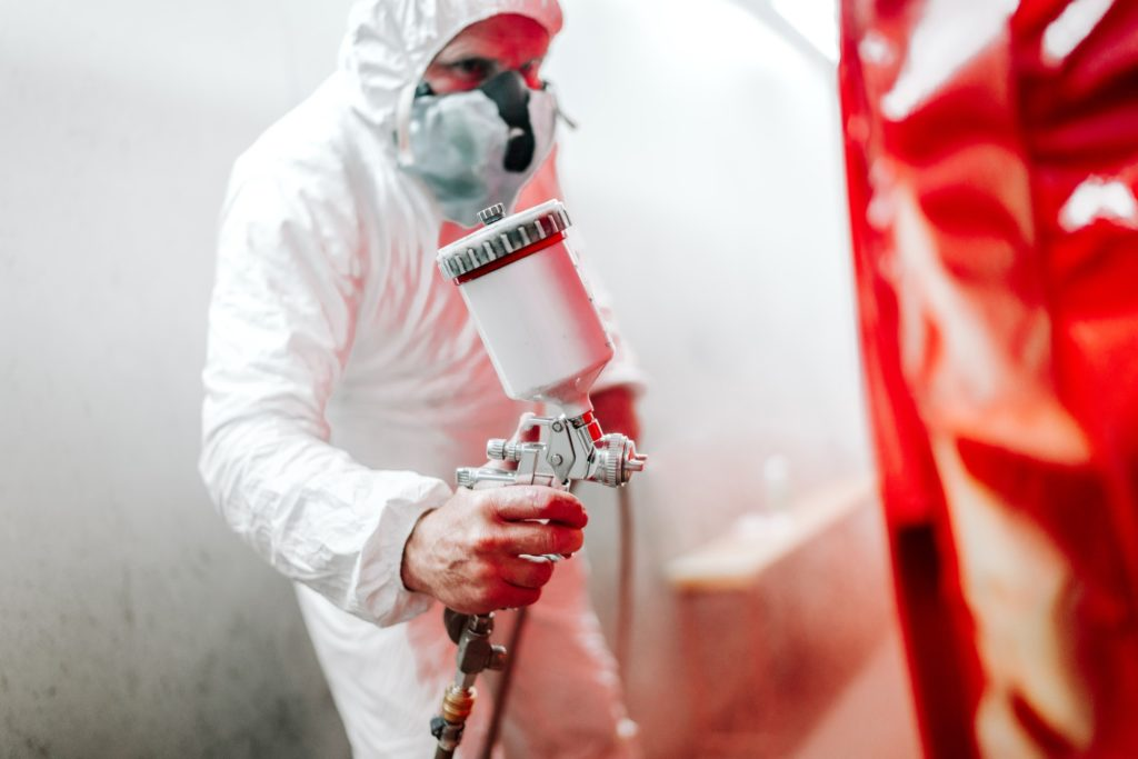 car painting details in automotive manufacturing industry. worker painting a car in special booth